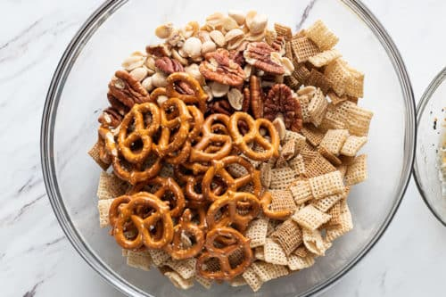 Chex cereal, pretzels, and nuts in a bowl