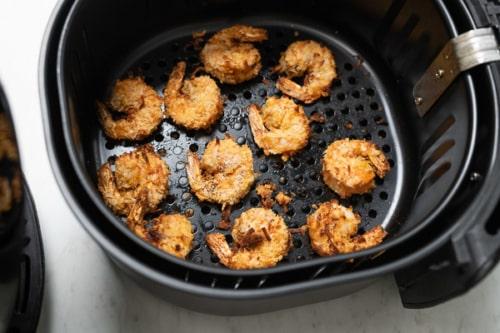 Cooked coconut shrimp in air fryer basket