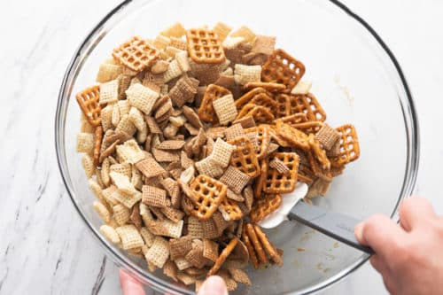 Cereal, pretzels, and peanuts being mixing into the seasoning