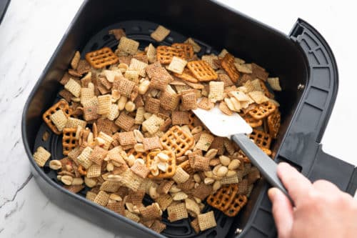 Snack mix spread out into even layer in air fryer basket