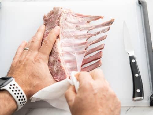 Peeling silver skin from back of lamb chop