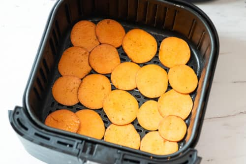 Uncooked sweet potato slices in air fryer basket