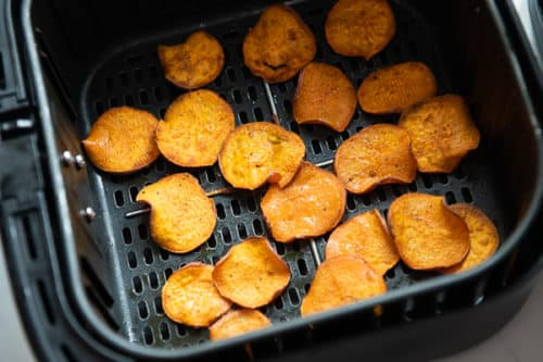 Partially cooked sweet potato chips in air fryer basket
