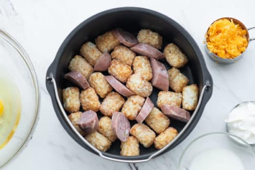 Layer tater tots and sausage in air fryer