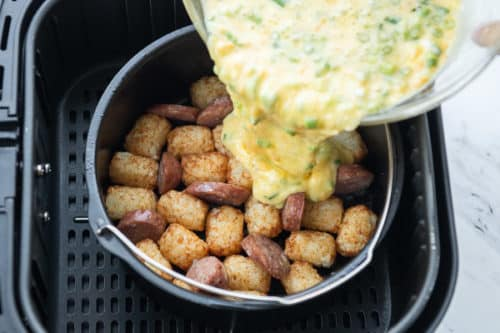 Add egg to air fryer with sausage and tater tots
