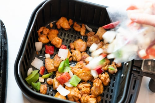 Adding vegetables to air fried chicken in air fryer