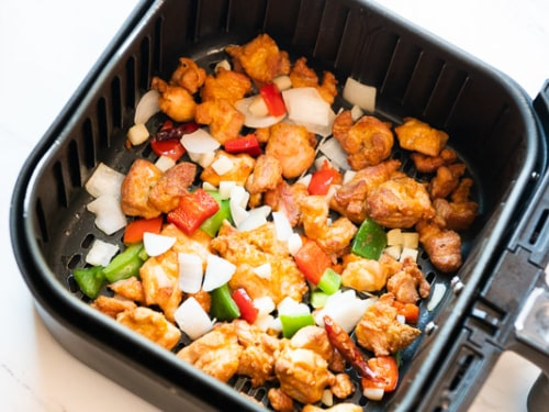 Cooked Chicken and vegetables in air fryer basket