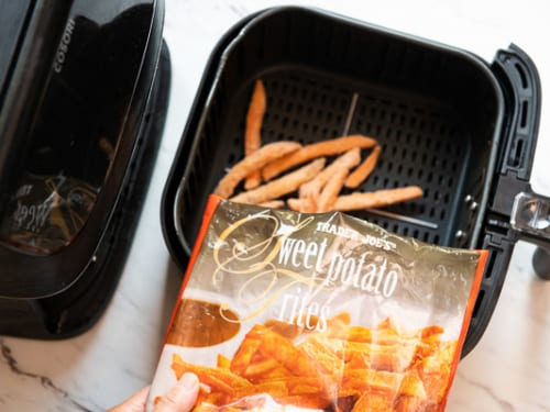 Bag of trader joes frozen sweet potato fries pouring into air fryer basket