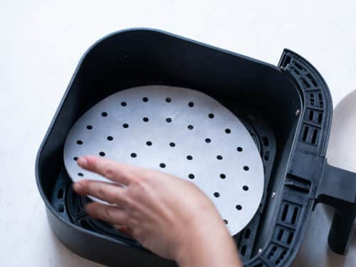 Lining air fryer with perforated parchment paper